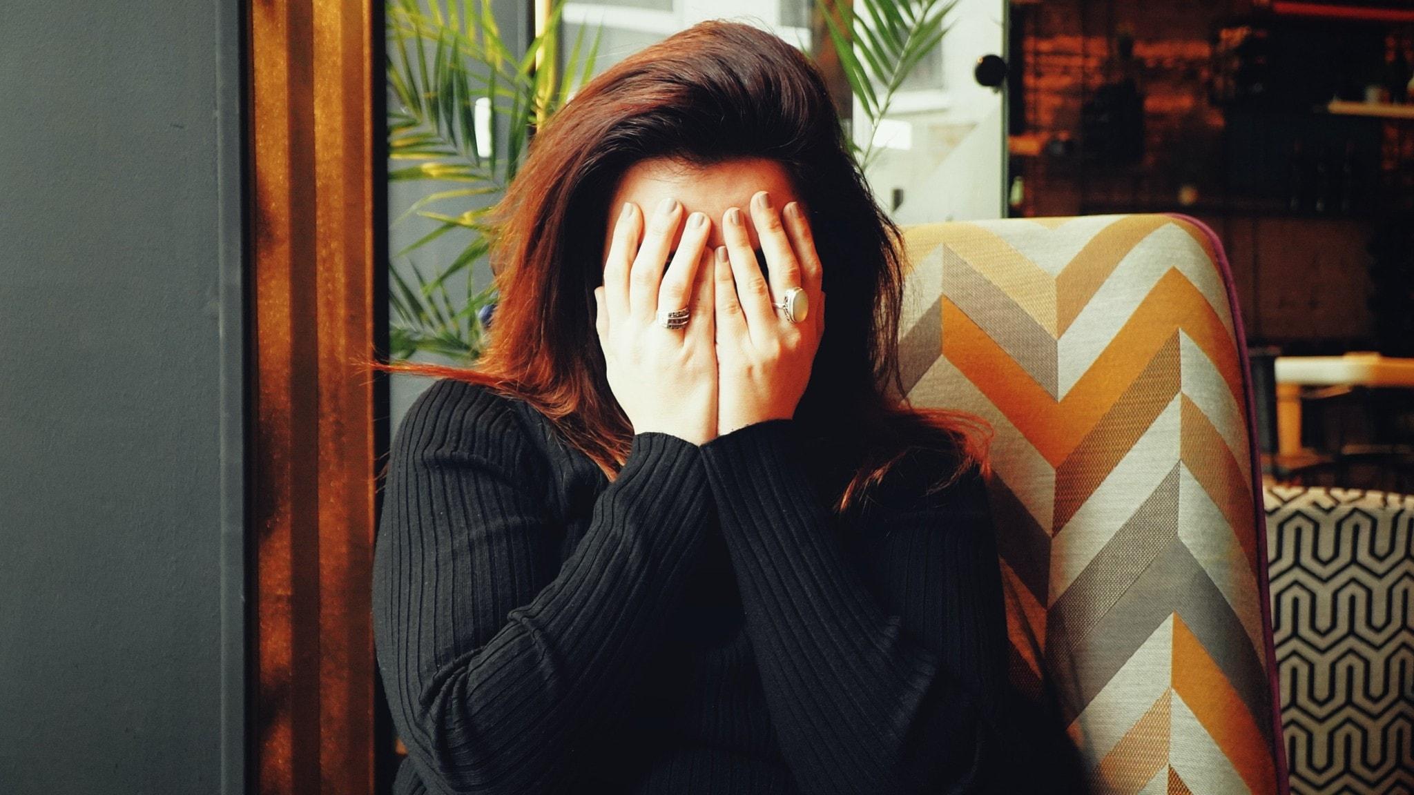 En kvinna håller händerna för ansiktet och gråter. Kvinnan har på sig en långärmad svart tröja. Håret är utsläppt och brunt och hon sitter i en flerfärgad stol.