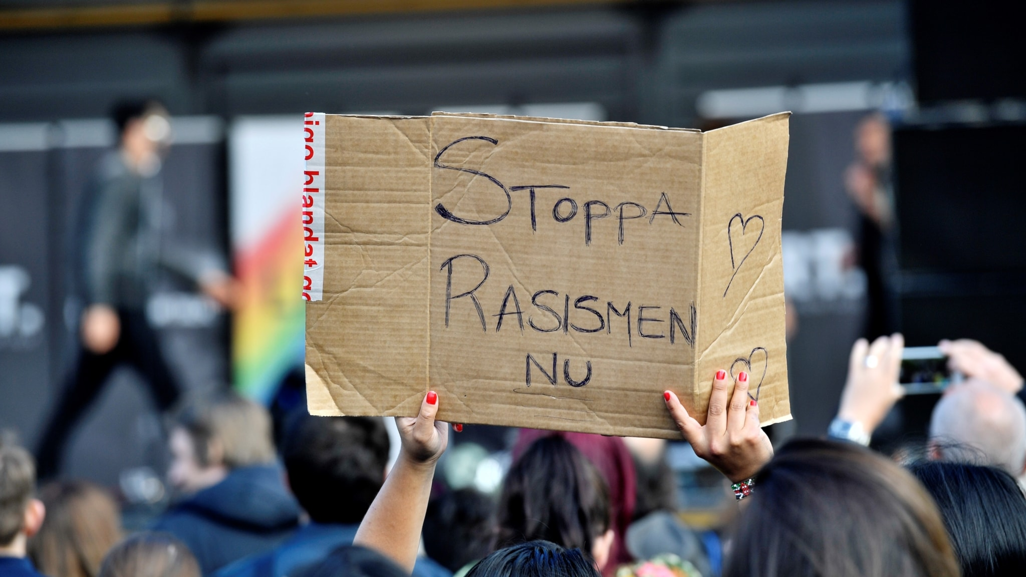 """En person håller upp en kartongbit med texten """"Stoppa rasismen nu"""""""