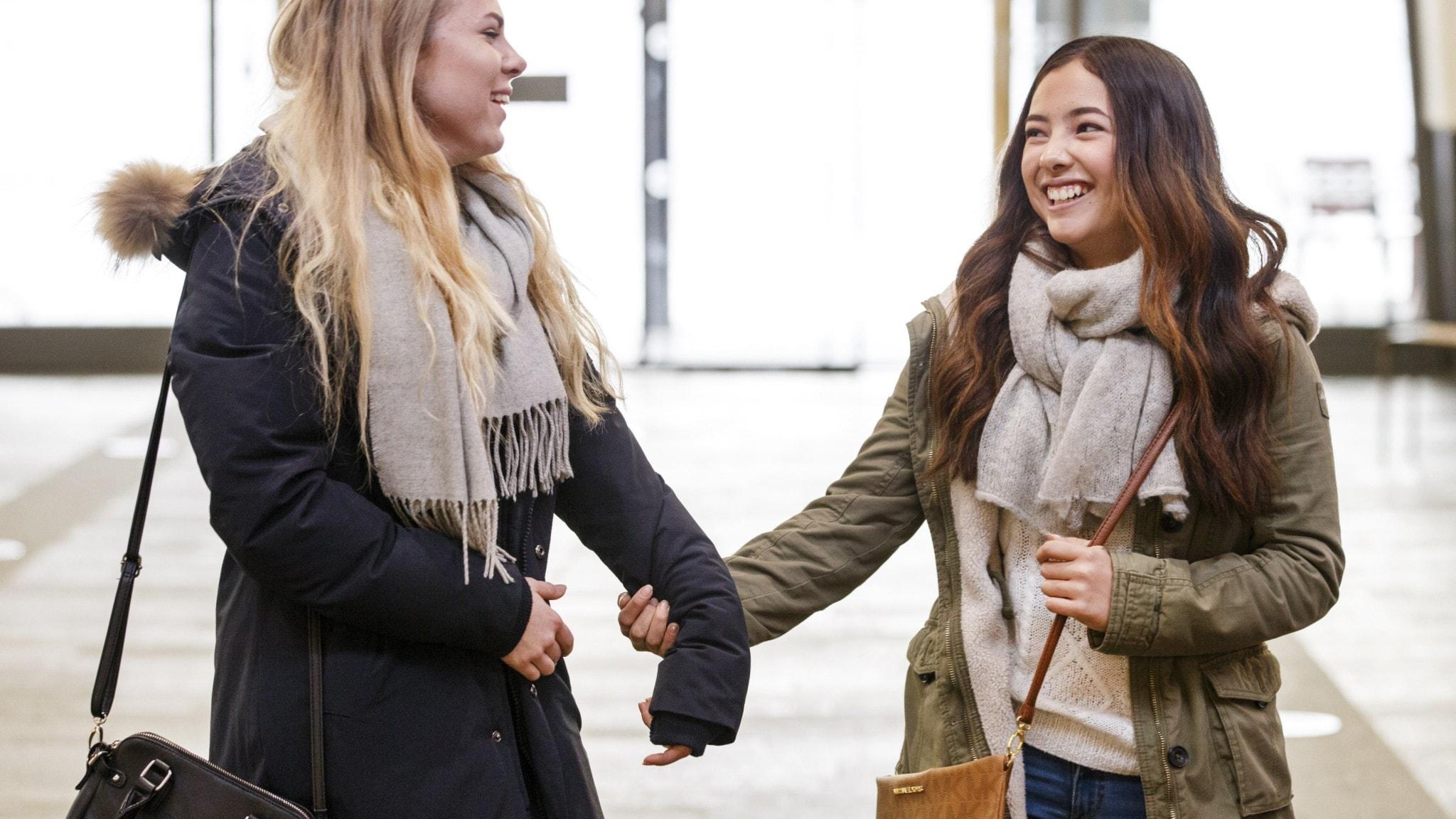 två unga kvinnor hand i hand