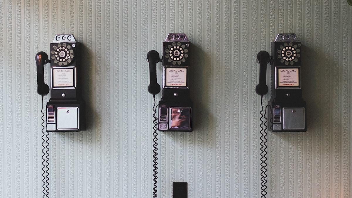 Tre gammaldags telefoner på rad på en grå vägg.