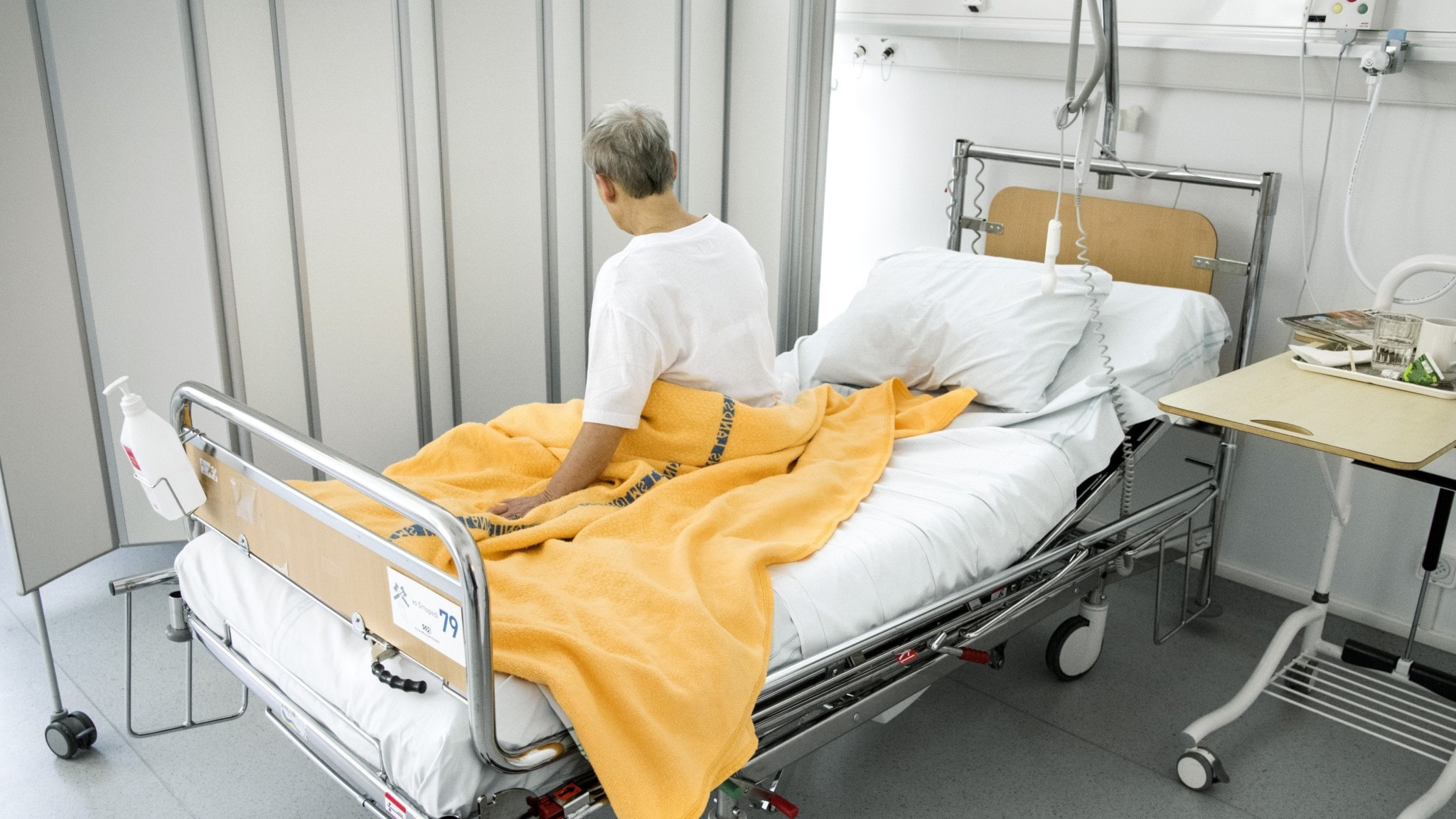 En person sitter i en sjukhussäng.