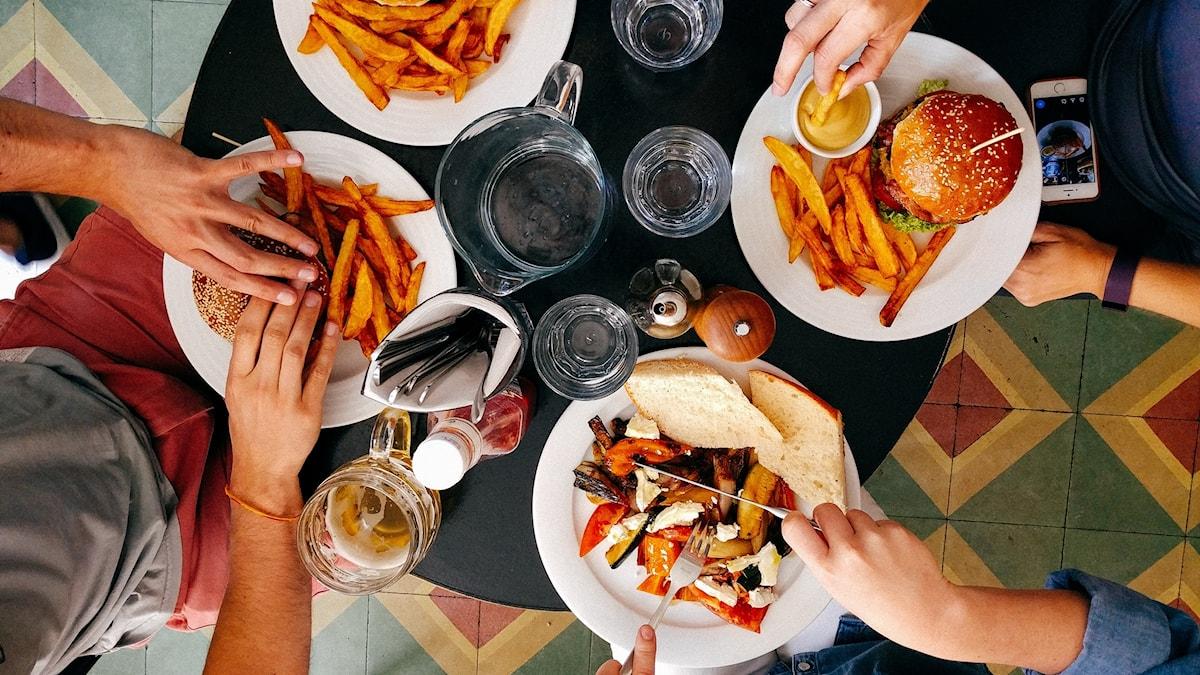 ett matbord med hamburgare, fyra par händer sträcker sig efter maten
