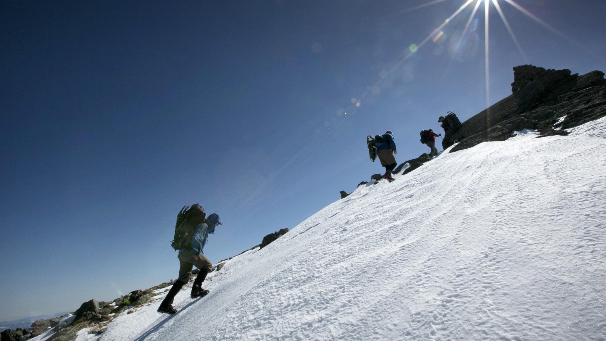 Man klättrar på ett snötäckt berg, solen skiner