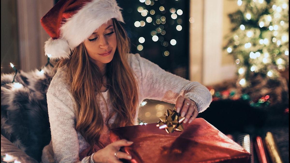 En kvinna i tomteluva öppnar en stor julklapp