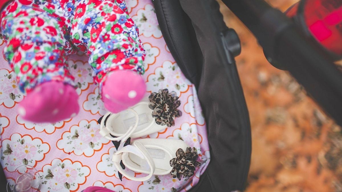 Bäbis fötter i en barnvagn. Små skor i barnvagnen.