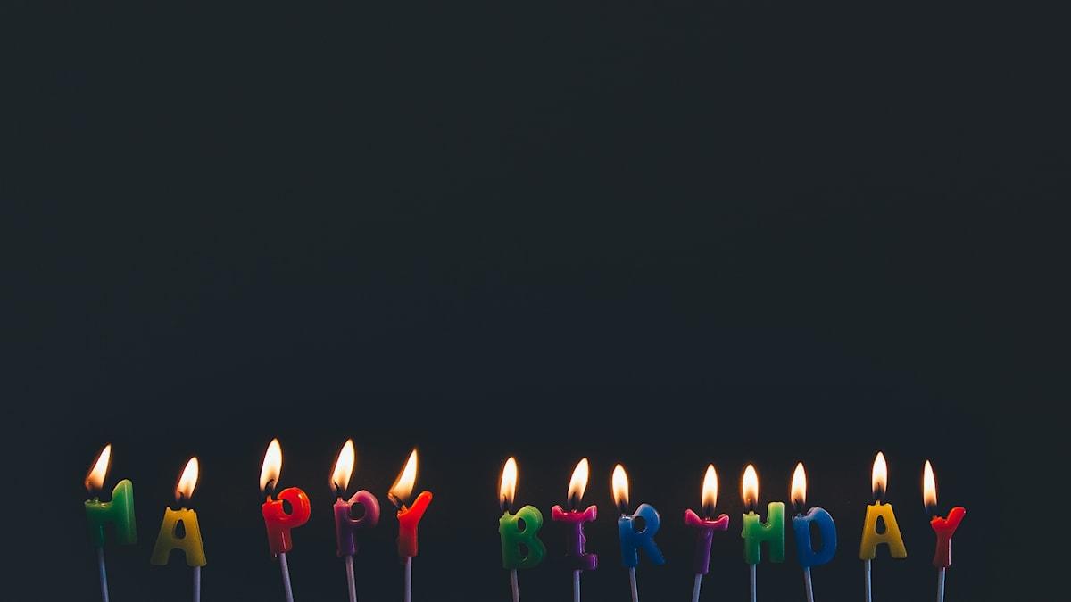 Färglada tända stearinljus som formar texten Happy birthday i en mörkt rum.