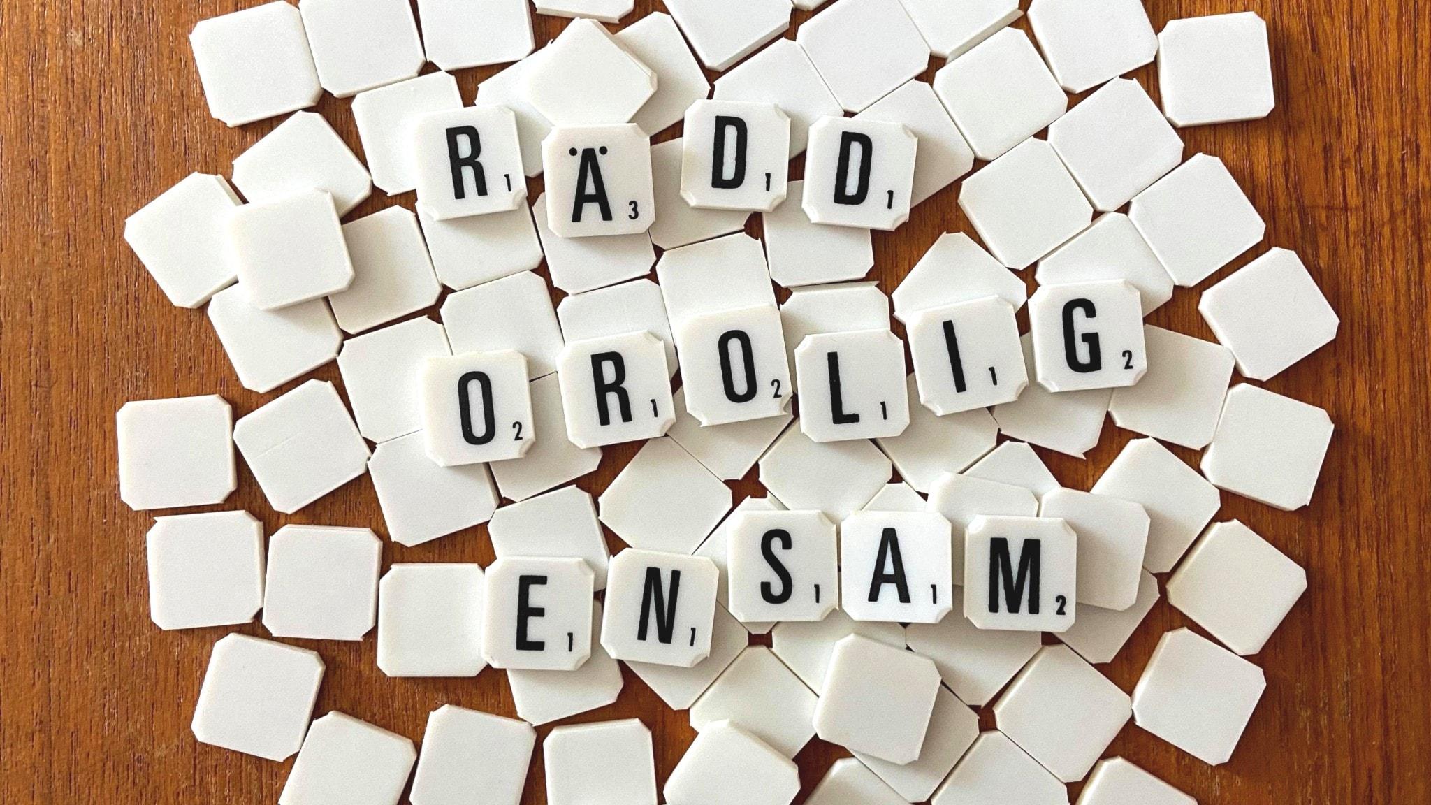 Brickor med bokstäver ligger på ett bord. De bildar orden RÄDD, OROLIG och ENSAM.