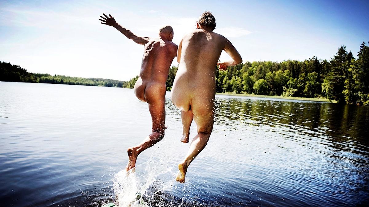 Två nakna människor hoppar från en brygga.