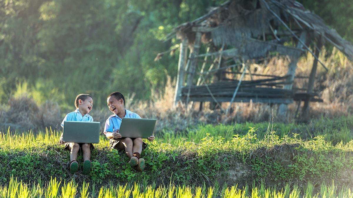 två små barn med en laptop
