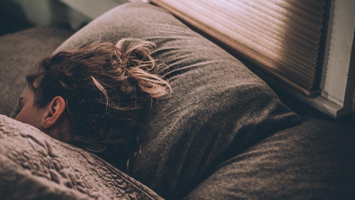 Person som ligger och sover i en säng.