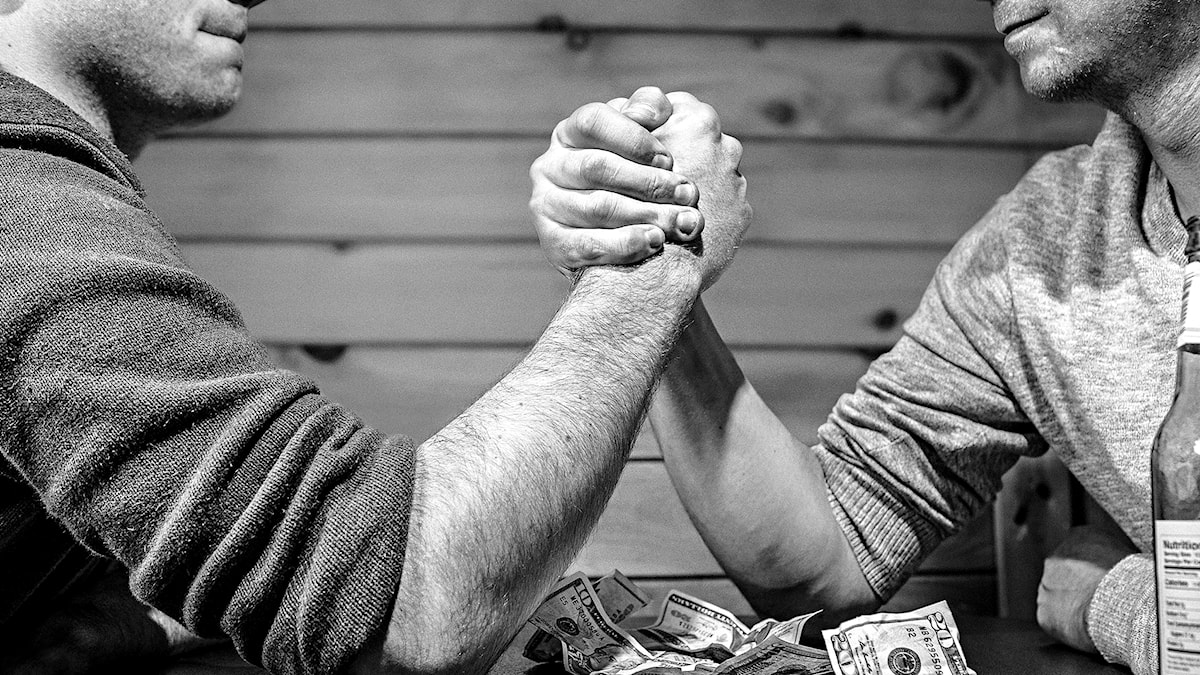 Två män bryter arm ovanför en bunt med sedlar.