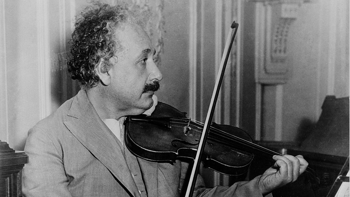 En svartvit bild på Albert Einstein där han spelar på en fiol.