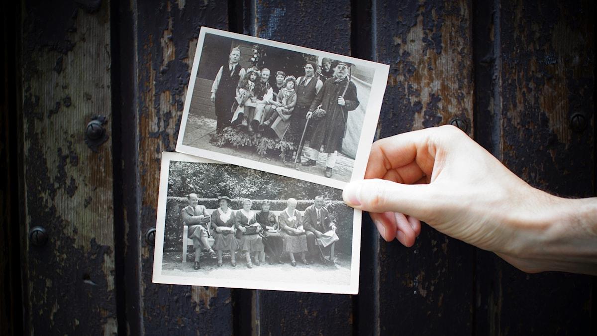 en hand håller upp två svartvita fotografier med familjeporträtt.