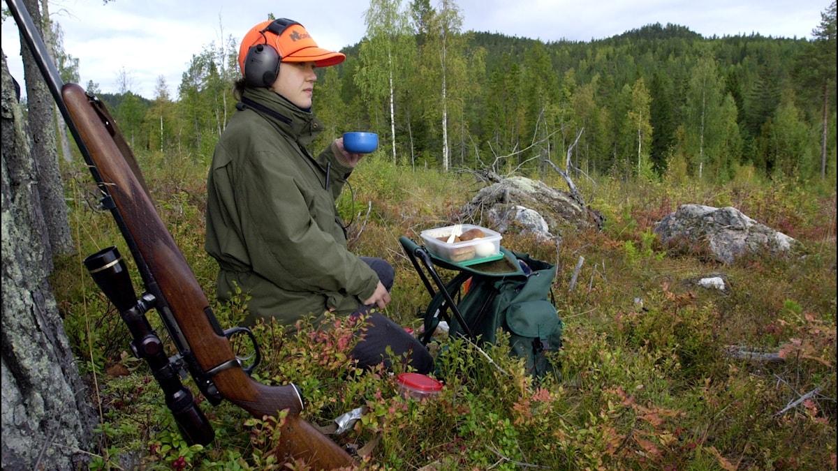 En kvinnlig älgjägare som tar en fikapaus på passet