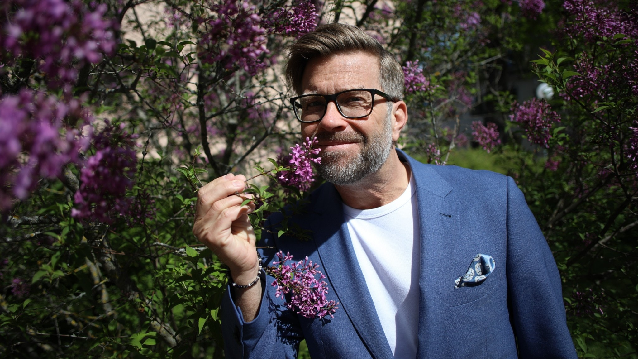 Programledare Bosse har på sig blå kavaj med vit t-shirt under. Han står framför en lila syrenbuske som han luktar på.