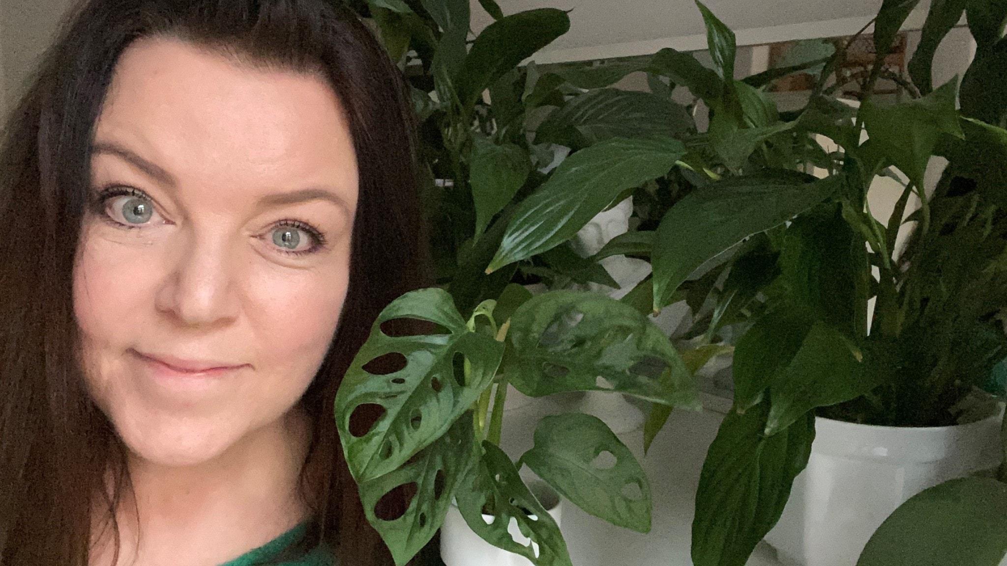 Mona Wahlund står framför krukväxter och ler.