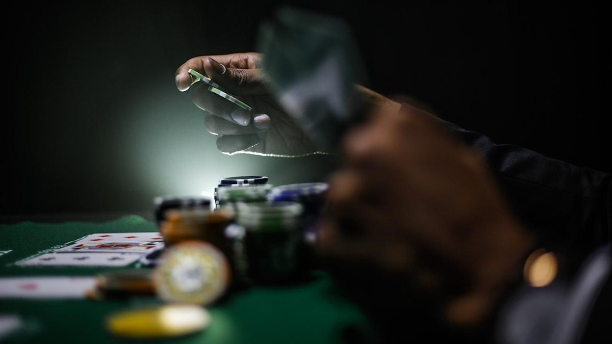 En närbild av ett mörkt spelbord med två händer, pokermarker och spelkort