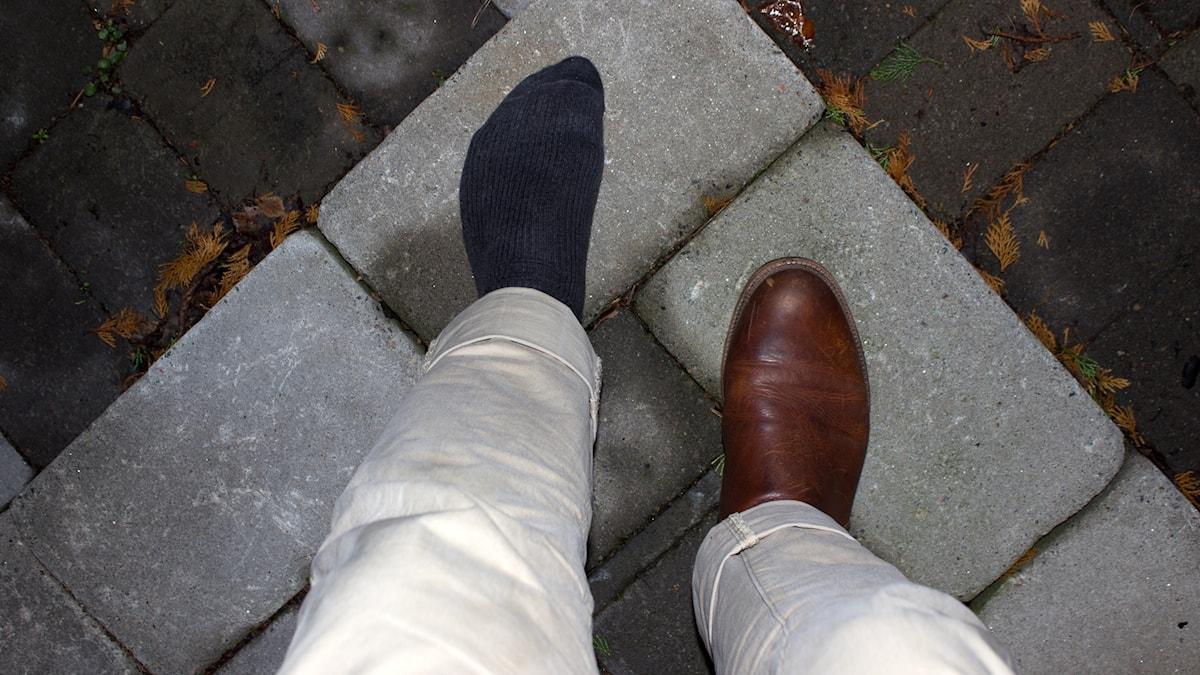 Två ben på en stentrappa med sko på en foten