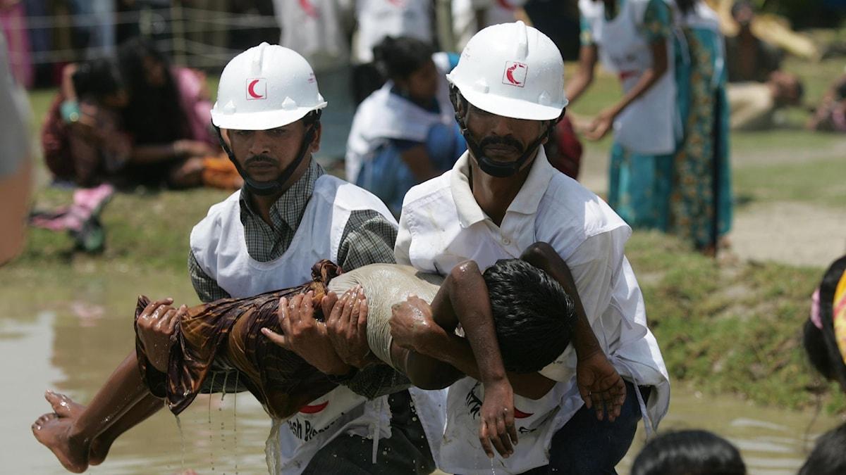 Två män i vita hjälmar övar på att lyfta ett barn ur vatten