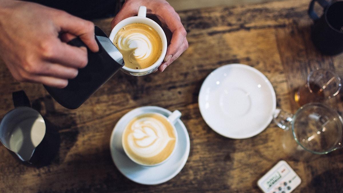 En hand häller grädde i en kaffekopp bredvid en annan kaffekopp.