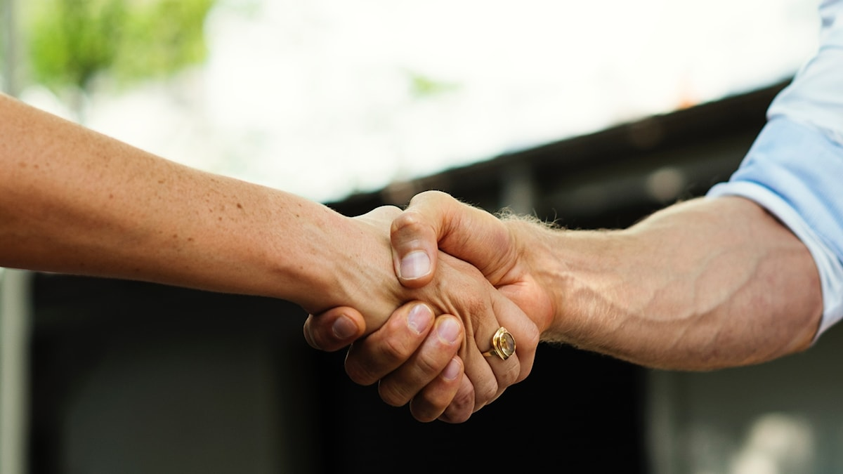 En man och en kvinna skakar hand.
