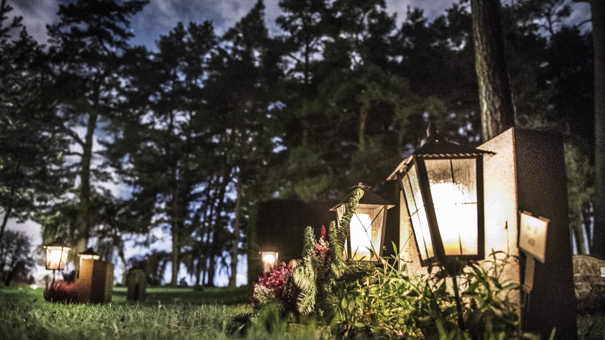 Kyrkogård med gravar och ljus i skymning