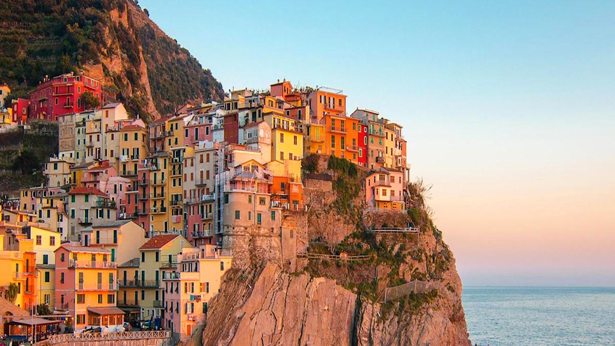 Bild på italienska Cinque terre. Färgglada hus som klättrar på en bergsvägg i soluppgång.