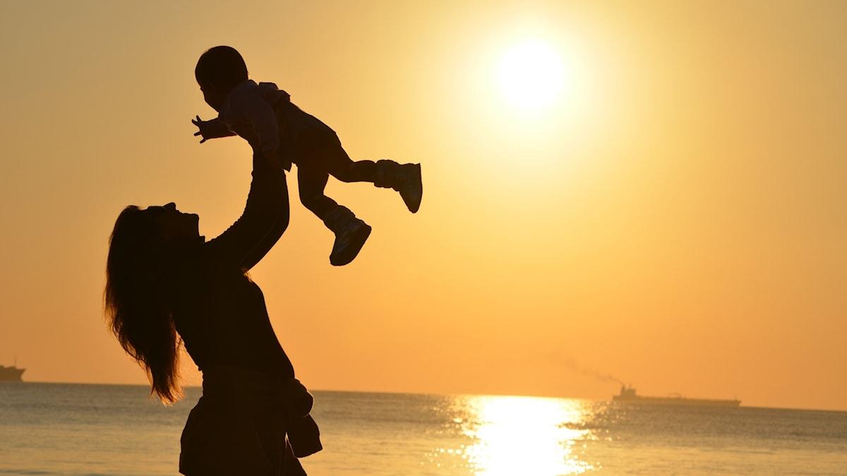 Mamma och barn i solnedgång.
