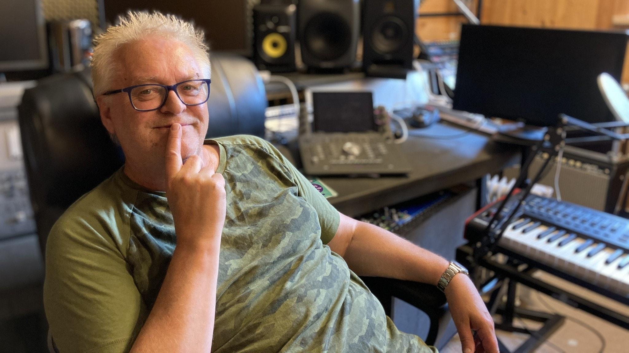Nick Borgen sitter i sin musikstudio. Instrument syns i bakgrunden.