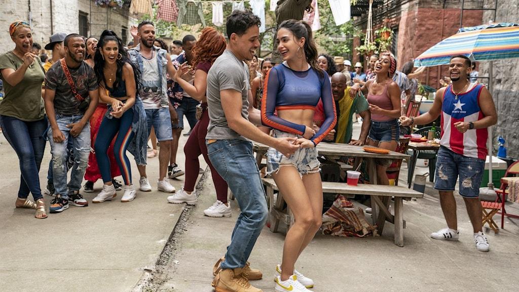 En man och en kvinna dansar på en gata, i bakgrunden jublar flera andra personer.