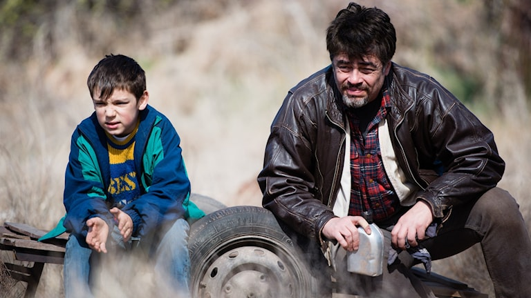 Benicio del Toro med en pojke han möter i A Perfect Day. Foto: TriArt.