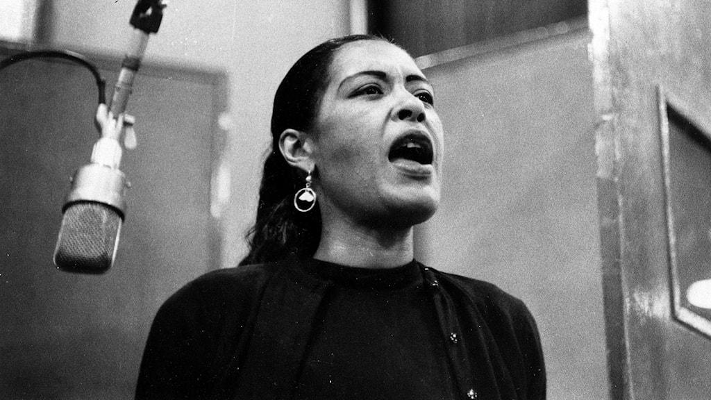 Sångerskan Billie Holiday i en svartvit bild där hon står i en studio vid en mikrofon