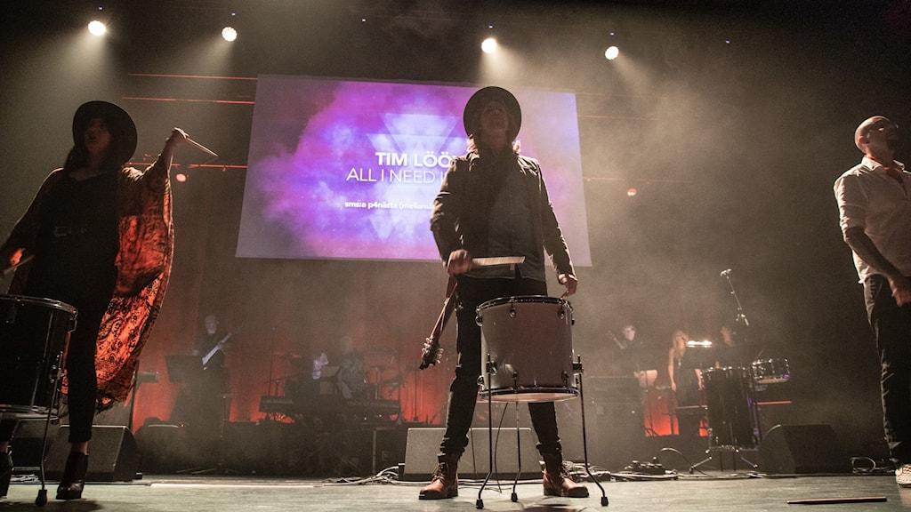 Tim Lööv står och spelar trumma i motljus på P4 Nästa finalens scen.
