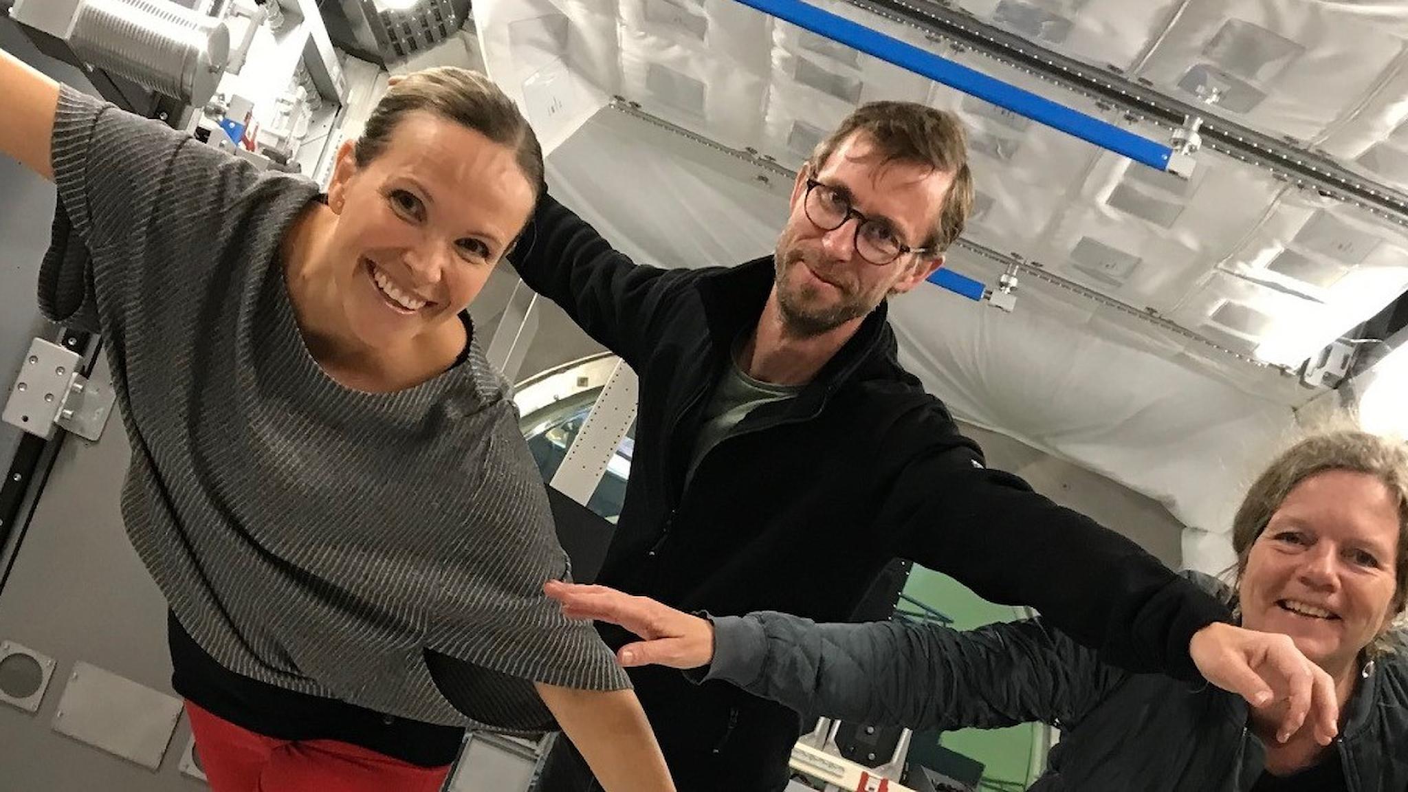 Tre personer tittar in i kameran med armarna utsträckta och kanske ser det lite ut som att de är tyngdlösa där de poserar inne i en fullskalemodell av den internationella rymdstationen.