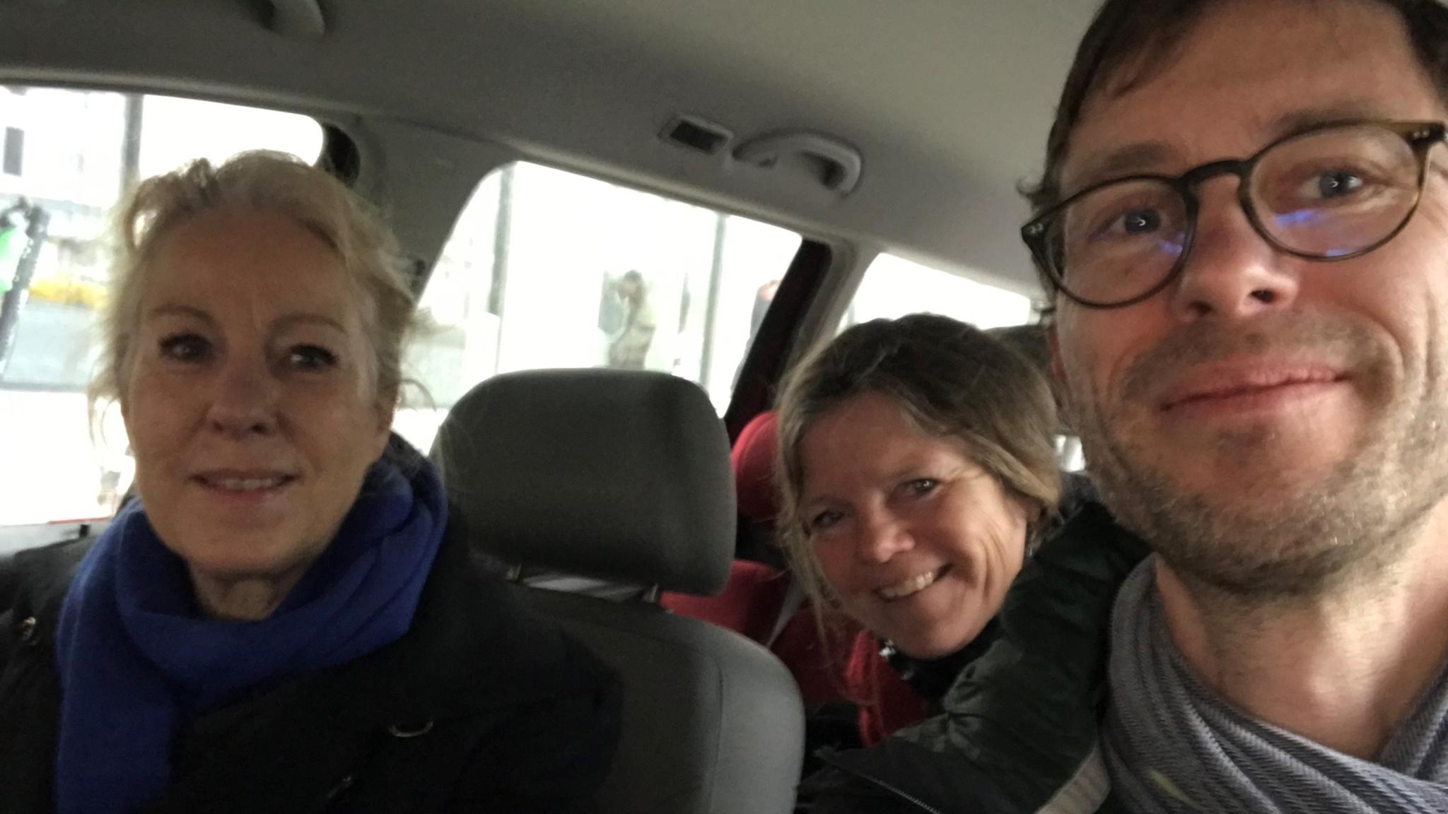 Tre personer sitter i en bil och ser glada ut.