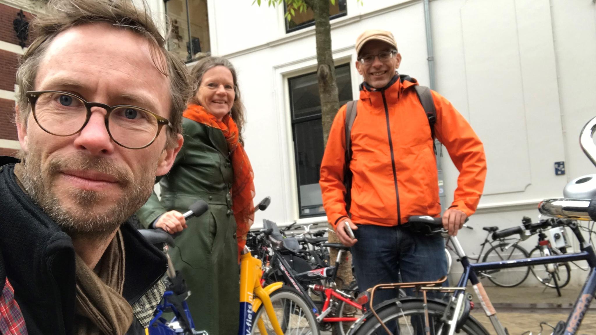 Närbild på Björn, men Lena och cykelexperten Herbert i bakgrunden, bland en massa cyklar i en stad.