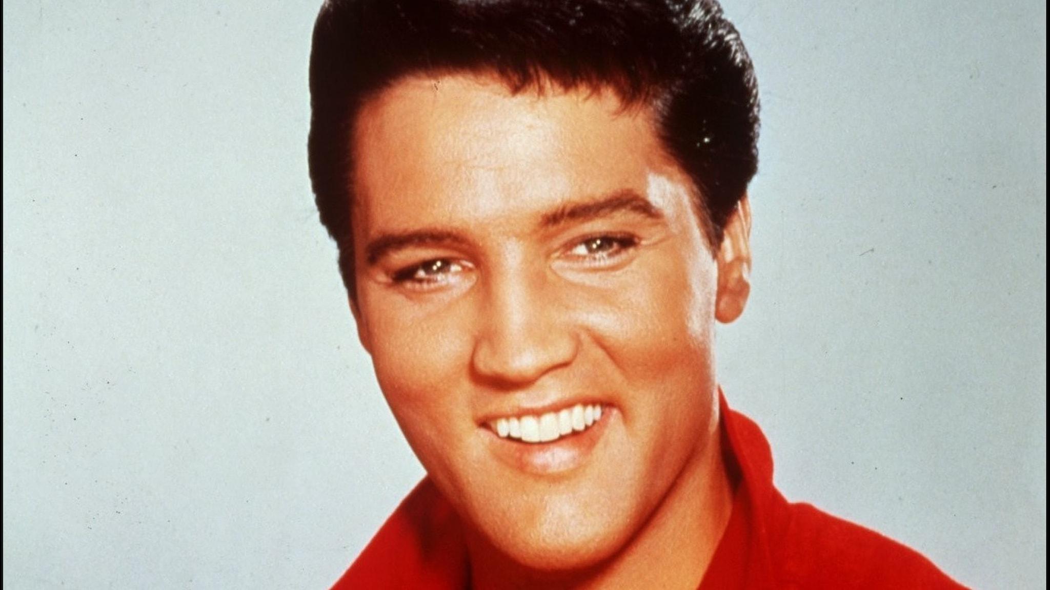 Ett porträtt på Elvis Presley med brett leende.