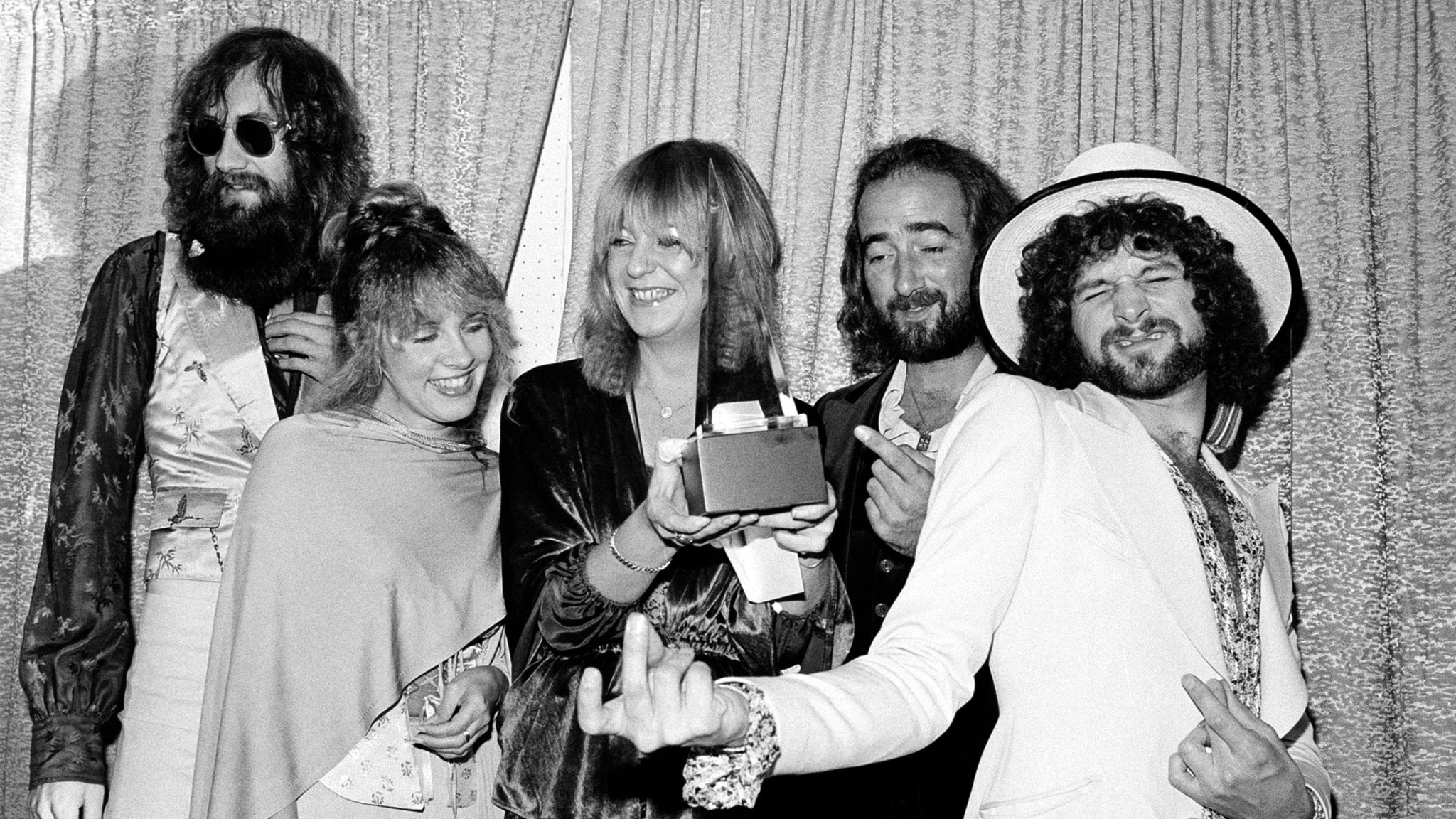 """Members of the singing group Fleetwood Mac pose with their award at the American Music Awards show in Santa Monica, Ca., Jan. 16, 1978.  The group was named favorite pop group and """"Rumours"""" was named favorite album in the pop category.  Posing from left are, Mick Fleetwood, wearing sunglasses; Stevie Nicks; Christine McVie; John McVie; and Lindsey Buckingham."""