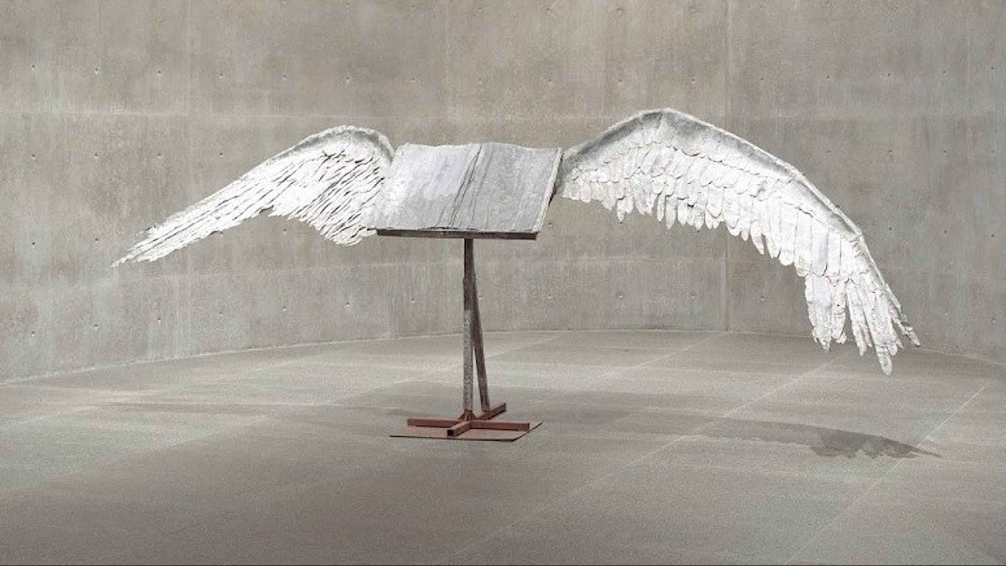 Staty av en uppslagen bok i silvrig metall försedd med två stora vingar.