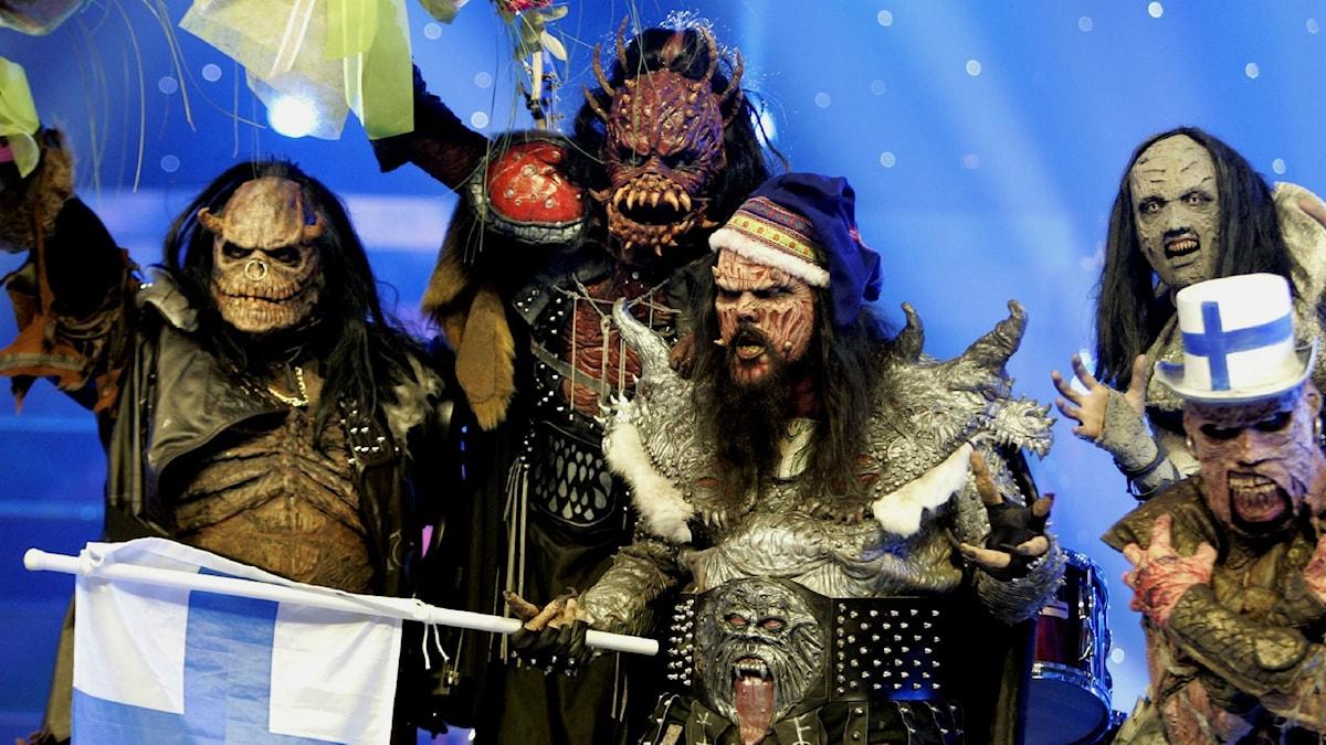 En bild på gruppen Lordi från Eurovision 2006 när de vann för Finland. De bär sin utstyrsel och håller i den finska flaggan.