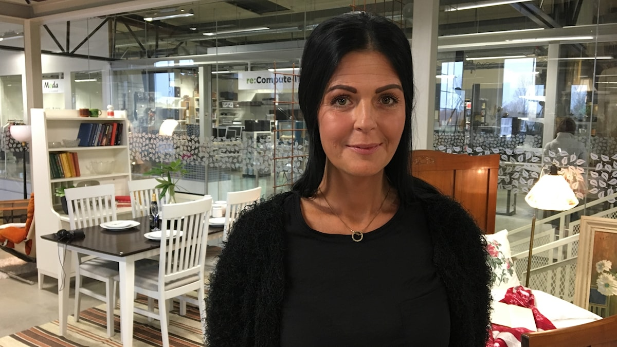 En kvinna i svart tröja står i en möbelaffär.
