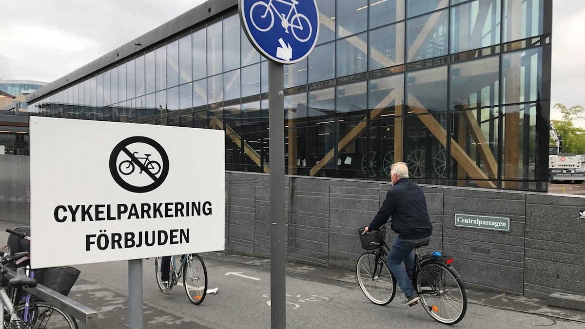 """Skylt """"cykelparkering förbjuden"""", skylt för cykelkörbana, man på cykel och i bakgrunden ett nybyggt glashus."""