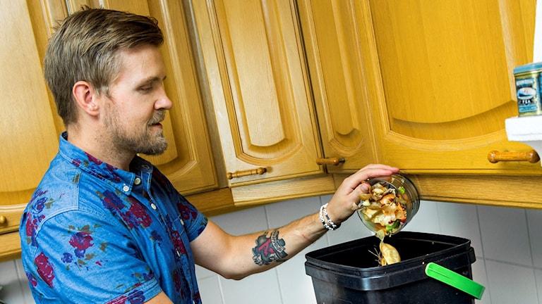 man i blå skjorta häller matavfall i en svart komposthink