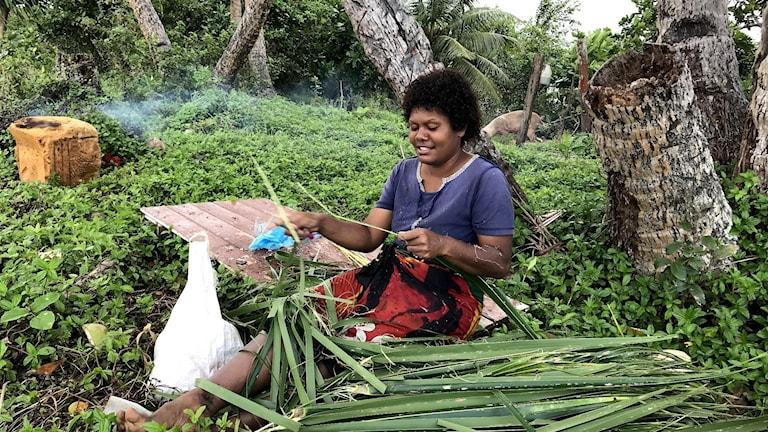 Mereiia Luse i byn Vunidogoloa på Fiji saknar havet som hon bodde vid fram till för fem år sedan innan hela byn evakuerades på grund av stigande havsnivåer. Hon kommer till stranden dagligen för att fiska eller som här, tillverka sopkvastar av palmblad.