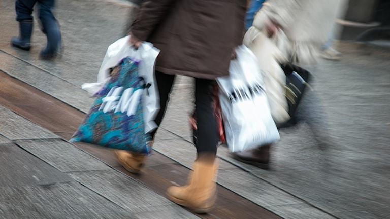 kvinna går på gata u brun kappa med flera plastpåsar i händerna