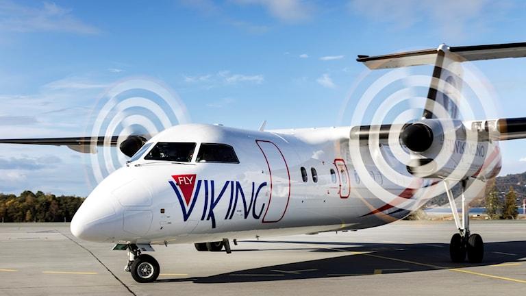 Litet vitt propellerplan med texten Viking står på marken med snurrande propellrar.