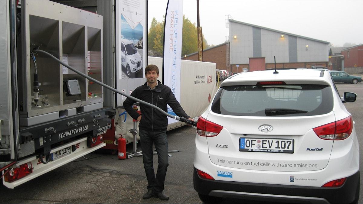 Projektledaren Daniel Ros på Sandvik tankar vätgas på fabriksområdet i bränslecellsbil. Foto: Johan Bergendorff / Sveriges Radio