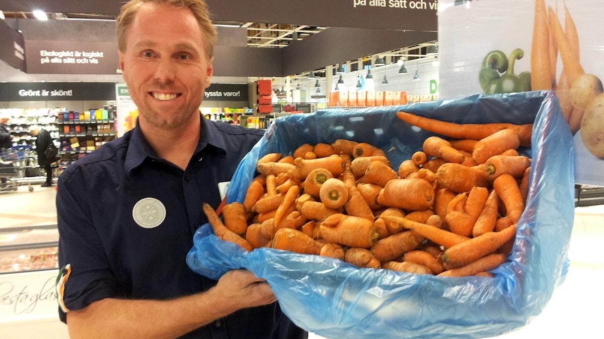 Anders Olsén som jobbar i en matbutik visar morötter med vissa defekter som säljs till rabatterat pris. Foto:Björn Gunér/SR