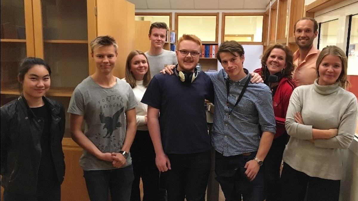 Elever från Erik Dahlbergsgymnasiet står i en grupp i uppehållsrum med bokhyllor i bakgrunden