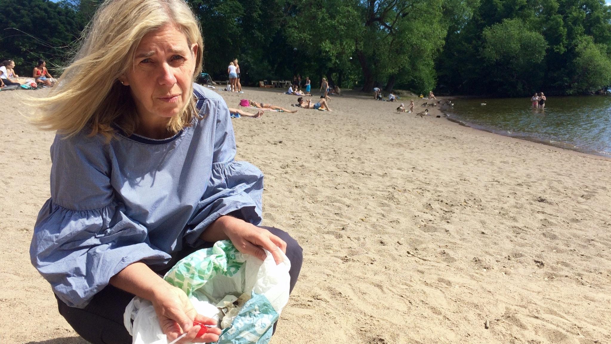 En kvinna sitter på en strand och lägger plastskräp i en plastpåse